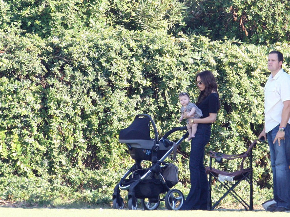 Victoria Beckham keeps baby Harper in the shade while they watch the boys playing soccer .