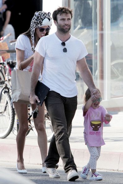 Supermodel Alessandra Ambrosio puts on a furry leopard hat as she walks with her husband Jamie Mazur and daughter Anja Louise