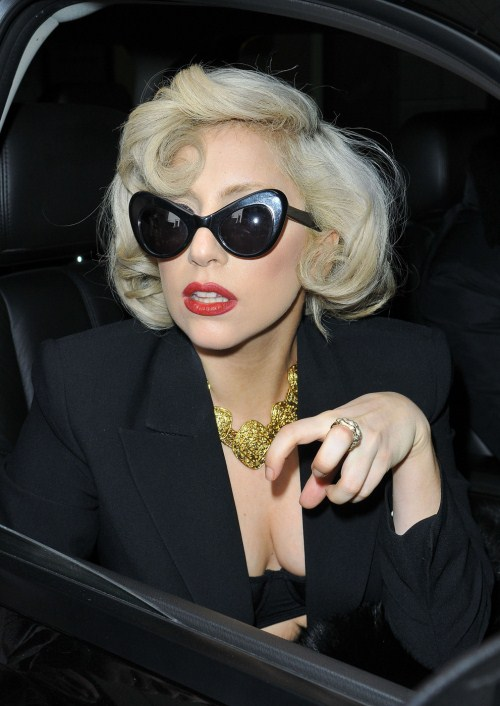 Monday December 12, 2011. Lady Gaga signs autographs for her fans as she leaves her New York City hotel. The pop superstar was seen wearing a pair of cat eye sunglasses as well as a black blazer with just a black bra underneath.