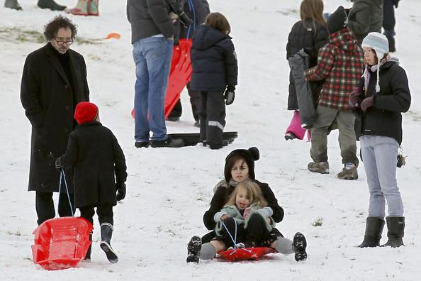 Tim Burton and Helena Bonham Carter take advantage of the snowfall in London by sledding with their kids on Primrose Hill.