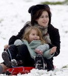 Tim Burton and Helena Bonham Carter take advantage of the snowfall in London by sledding with their kids on Primrose Hill.