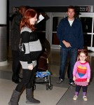 Alyson Hannigan shows off a huge baby bump as she arrives at JFK Airport in New York with husband Alexis Denisof and daughter Satyana.