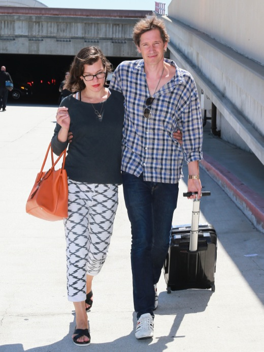 Pregnant Milla Jovovich Touches Down At LAX With Her Husband