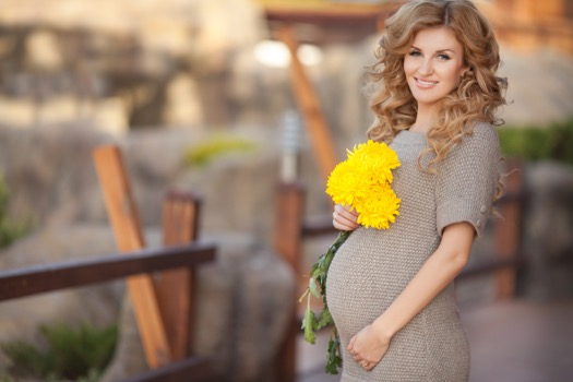 Beautiful pregnant woman with spring flowers outdoor