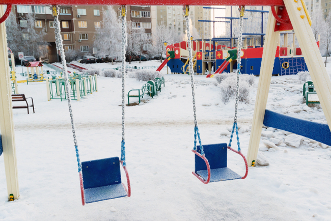 snow covered swing and slide at playground in winter