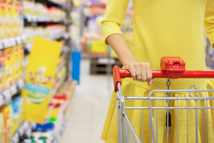 Young woman shopping for baby food in supermarket